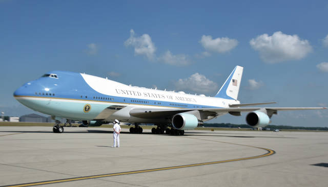 A United States Navy officer greets Air Force One as it taxis on the ramp at Wright-Patterson Air Force Base during President Trump's visit to Dayton on Wednesday.