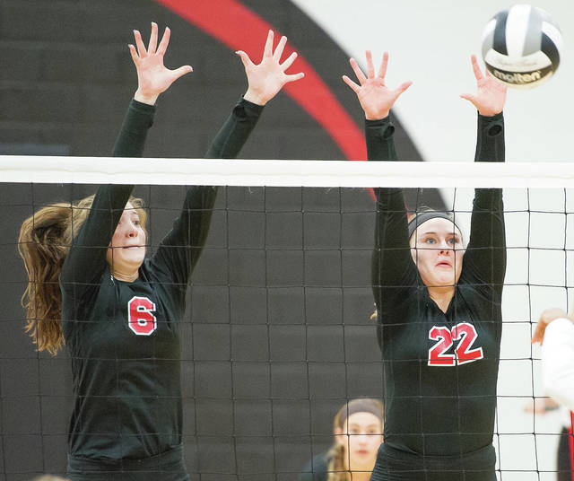 Fort Loramie outside hitter Marissa Meiring, right, and sophomore middle hitter McKenzie Hoelscher go for a block during a Division IV sectional semifinal on Oct. 20, 2018 in Covington. Meiring, a senior, had 248 kills last season while Hoelscher, a junior, had 87 kills due to being injured most of the season.