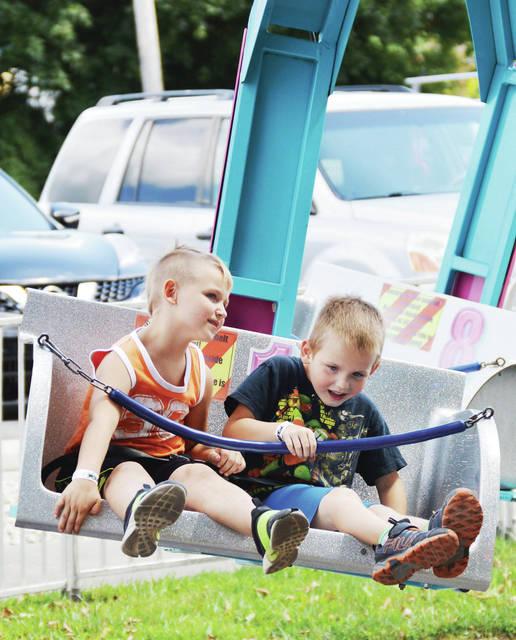Coby McFarlin, left, 6, of St. Marys, son of Jake McFarlin and Maddy Schoer, and Caleb McFarlin, 6, of DeGraff, son of Mike and Sarah McFarlin, take a spin on a ride at the De Graff Country Fair on Saturday, Aug. 24.