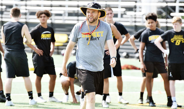 Sidney coach Adam Doenges watches a drill during a practice on Thursday morning at Sidney Memorial Stadium. It was the first day of practice for all prep sports teams throughout Ohio, though the Yellow Jackets have been on the field since Monday by using the last of their 10 summer coaching days permitted by the OHSAA.