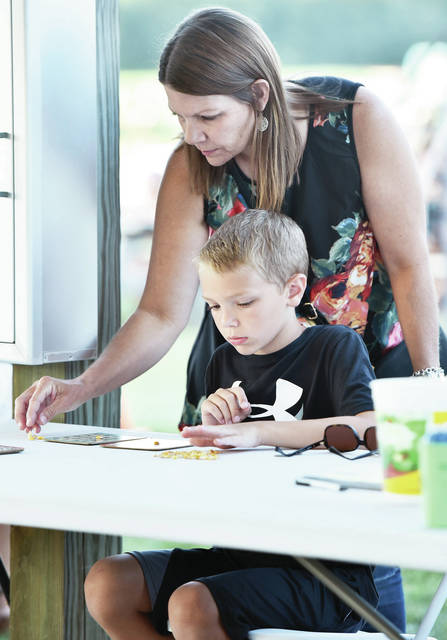 Michelle Noll, helps her son, Brady Noll, 8, both of Anna, son of Mark Noll, set-up his boards for a game of bingo at the Sacred Heart Church's annual picnic in McCartyville on Saturday, Aug. 10.