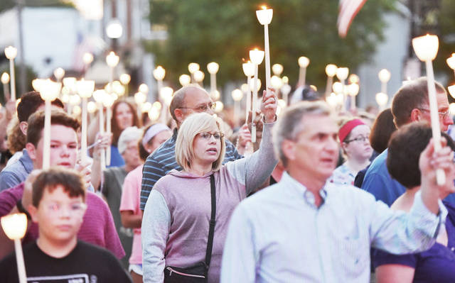 People hoist candles as they sing during a candlelit Marian Rosary Procession in Botkins on Thursday, Aug. 15.