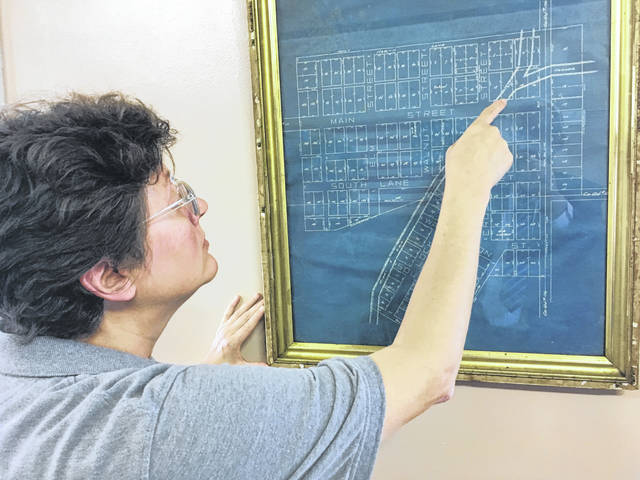Lockington Mayor Tracy Johnson looks at a plat map of the Village of Lockington that shows the Miami & Erie Canal bisecting the village. The map hangs on one wall of the Lockington Village Hall. Founded as Locksport in 1837, the village was incorporated as Lockington in 1858.