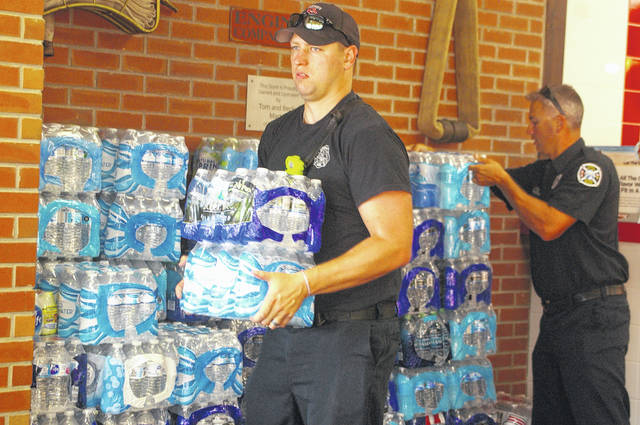 Firefighter Andy Zumberger, left, and firefighter Mike Utz, right, carry water from Firehouse Subs to a Sidney Fire Department truck waiting outside on Monday afternoon. Firehouse Subs in Sidney donated 112 cases of water to the Sidney Fire Department as part of its H2O For Heroes promotion.
