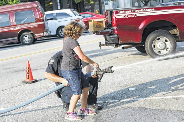 Jaedlyn Hansen, with assistance from Sidney firefighter Jason Truesdale, practices putting a fire out during the 2017 National Night Out. She is the daughter Joseph Hansen, of Sidney.
