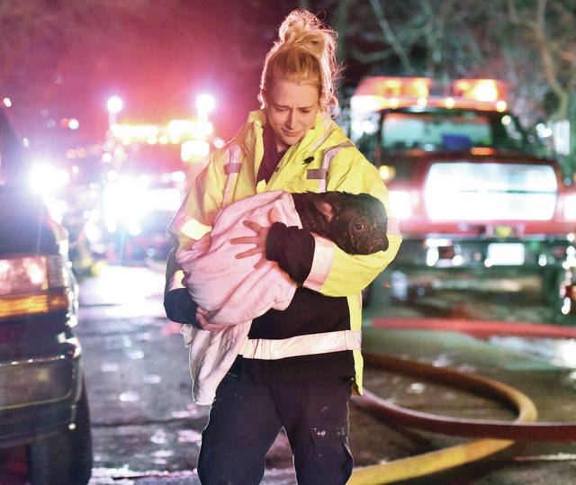 Perry Port Salem Rescue EMT Kelsey Beam carries a wet dog away from a house fire at 223 N. Walnut Ave. in Sidney late March 26. Responding to the fire were the Sidney Fire Department, Botkins Fire Department, Anna Fire Department, Lockington Volunteer Fire Department and the Van Buren Fire Department. The fire took more than an hour to fully extinguish.