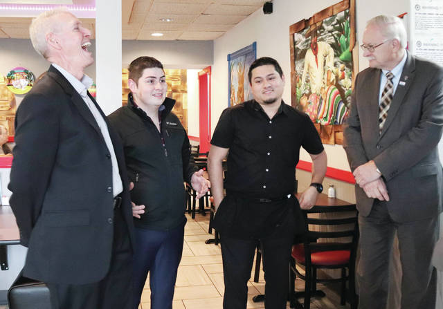 Owner-operators Juan Lopez, second from left, and Jonathan Fuentes, third from left, talk with President of the Sidney-Shelby County Chamber of Commerce Jeff Raible, left, and Sidney Mayor Mike Barhorst, right, during a ribbon cutting ceremony for Las Tapatias on April 30. The restaurant, located at 1306 Wapakoneta Ave. in Sidney, recently was renamed Mojitos.