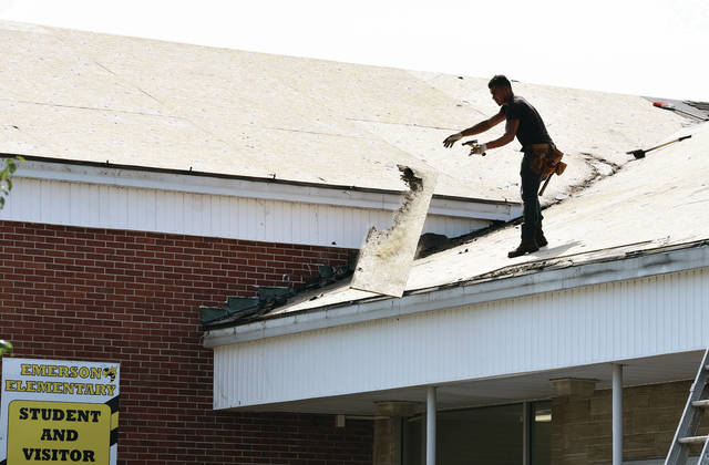 Raul Bills, of New Carlisle, tosses down a rotten piece of plywood from the roof of Emerson Elementary. The school is getting a new roof which will be finished in roughly a week.
