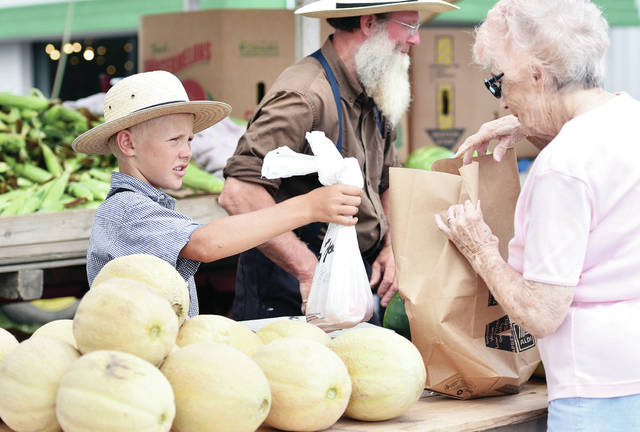 Joshua Warner, left, of Bradford, hands a bag of peaches to Dora McFarlan, of Sidney, at a produce stand in the parking lot of Cazadores on Thursday, Aug. 1. Warner was helping his grandpa Duane Garber, center, of Bradford, work the produce stand which sells sweet corn, green beans, onions, watermelons and red potatoes among other things.