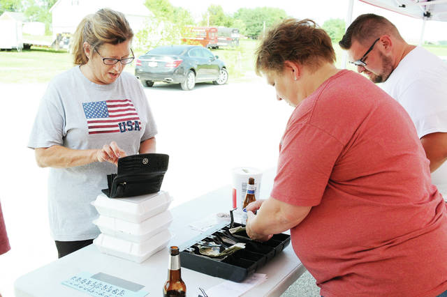 Patty Schlater, left to right, buys the last three chicken dinners from Patty Goldschmidt and Dustin Hickerson, all of Fort Loramie, during a Brandewie Family fundraiser at Al's Place in Fort Loramie on Sunday, Aug. 4. About 535 chicken dinners were sold out in only 45 minutes.