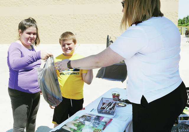 Kila Puckett, left to right, 13, and her brother Carter Puckett, 11, children of Kendra and Paul Driscoll, hand school supplies to Salvation Army Lt. Katie Mayers, all of Sidney, during School Tools Stuff the Bus program held in conjunction with Walmart on Saturday, Aug. 3. School supplies donated will be given to kids in the local community that need them.