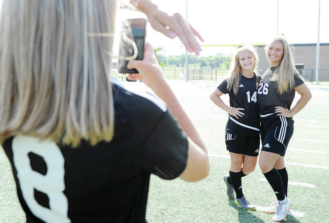 Megan Heckler, 17, daughter of Jim and Carol Heckler, photographs Jadah McMillen, 15, and her sister Khia McMillen, 16, all of Sidney, both of children of Julie and Scott McMillen. The three Sidney High School soccer players had been getting their fall sport photos taken Thursday and took some time to take their own photos.