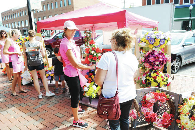 Barb Burton, left, shows Robin Knasel, both of Sidney, a bouquet of silk flowers for sale at the Memorial Silks by Barb stand during the Sidney Farmers Market on Saturday, Aug. 10.