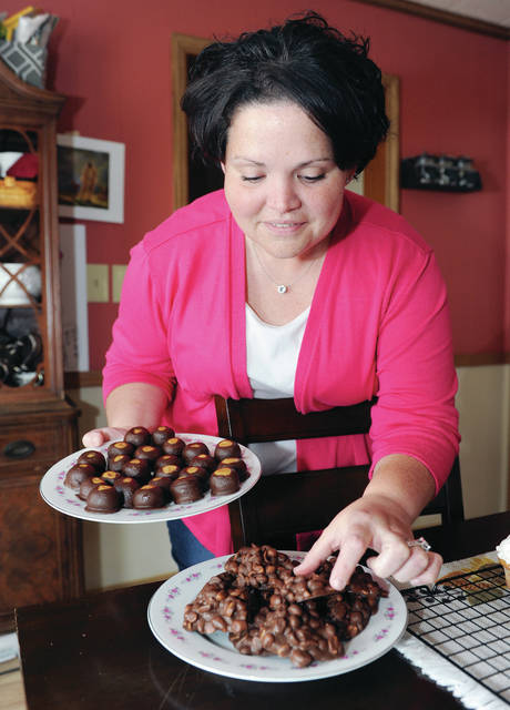 Megan Wade-Allen, of Sidney, holds a plate of Buckeyes while arranging a plate of peanut and chocolate clusters, both of which she made and is offering at her new business called Sweet Cheeks Confections.