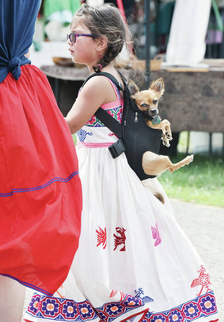 Tayna Evangelista, 5, of Springfield, daughter of Jessica and Lucas Evangelista, walks with her dog, Lucy strapped to her back at the 2019 Honor our Veterans & 1st Responders Powwow at the Shelby County Fairgrounds on Saturday, Aug. 17. Tayna is a member of the Huichol Tribe.