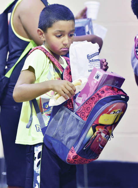 Camdyn Davis, of Sidney, son of James and Kristina Davis, gauges whether his bag of popcorn will fit in his new backpack filled with back to school supplies that he had gotten at the Salvation Army's Back to School Bash on Saturday, Aug. 17.