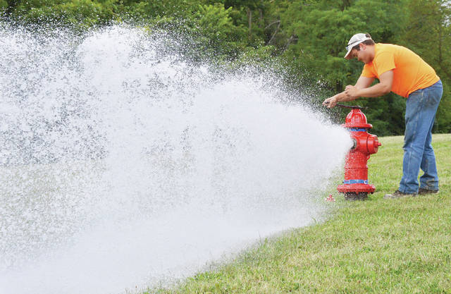 City of Sidney employee Andy Meyer, of Sidney, flushes a fire hydrant on Hoewisher Road just west of its intersection with Wapakoneta Avenue on Wednesday, Aug. 21.