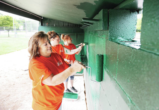 Painting the inside of a dugout at Veteran's Memorial Field are Piqua Home Depot employees, Tracy Clough, left to right, of Sidney, Amber Fields, of Englewood, and Kyrstyn Boyer, of Covington. The Piqua Home Depot employees also intsalled steel siding and and aluminum fascia along with a new door on the first base dugout storage room on Thursday, Aug. 22.