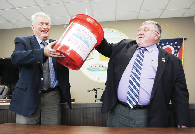 Shelby County Commissioner Bob Guillozet, right, draws the winning Shelby County Ohio Bicentennial raffle ticket from a bucket held by fellow Commissioner Tony Bornhorst. The winner, Catherine Burns, of Sidney, will receive over $700. The drawing was held at the Shelby County Commissioners Office on Thursday, Aug. 22.
