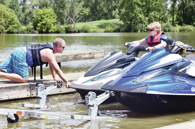 Mike Marion, left, gives his mom, Carol Marion's jet ski a push to help her get into Lake Loramie on Friday, Aug. 23. Mike Marion bought the three seat jet skis to replace his families old ones. Mike Marion got the three seat models so there would be room for his four sons when he and his wife took them out to the lake. The Marions are from Covington.