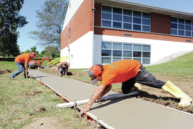 Working on a new sidewalk at Whittier Elementary are, left to right, Tom Taylor, of Sidney, Ben Trotter, of Troy, and Aaron Root, of Kenton. The new sidewalk extends from Broadway Avenue to the back door of Whittier Elementary where kids will enter for the Latchkey program this year. The Latchkey program gives kids a safe place to be before and after school. Without the sidewalk, Latchkey enrollees would have been contending with snow and wet grass to get to the door. John R. Lloyd Concrete Construction donated all the concrete and manpower for the project. Cutstone Inc. donated the gravel used.
