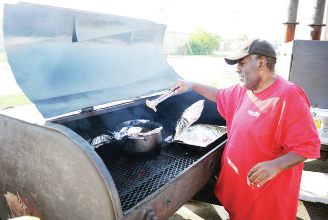 "Tommy Henderson, of Sidney, checks on a pot of rib tips he was cooking at The Lunch Bus located at the intersection of Campbell Road and South Vandemark Road on Friday, Aug. 30. The Lunch Bus sells BBQ chicken, pulled pork and sausage for main dishes. The Lunch Bus also sells a wide array of sides such as mac and cheese, baked beans, greens, cole slaw and loaded baked potatoes. The available sides changes. The business is owned by Lashonda Hixon and her brother, Korey Henderson, both of Sidney. The Lunch Bus mantra is ""The heavenly taste you don't want to waste."" The Lunch Bus has been around for about five months. Food is for sale on Thursday, Friday and Saturday, from 11 a.m. until the food runs out which is usually around 5 p.m. or 6 p.m.."