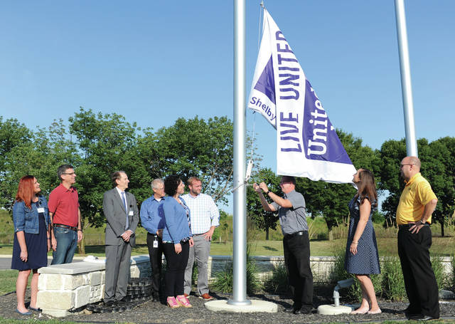 AME manager Mark Landis, seventh from left, of McCartyville, raises the United Way flag at Emerson on Friday, Aug. 30. Watching Landis are, left to right, United Way large manufacturing chair Suzanne Cline, of Sidney, Emerson Vice President of Human Resources Tom Sheehan, of Troy, President and CEO of Mutual Federal Savings Bank Dean Weinert, of Eaton, Emerson plant Manager - Air Conditioning Dave Conover, of Troy, Emerson Vice President of Human Resources Lisa Merritt, of Troy, Emerson Director of Human Resources Grant DeYoung, Emerson Human Resources Generalist Katy Zimpfer, of Botkins, and Shelby County United Way President Scott Barr, of Anna.