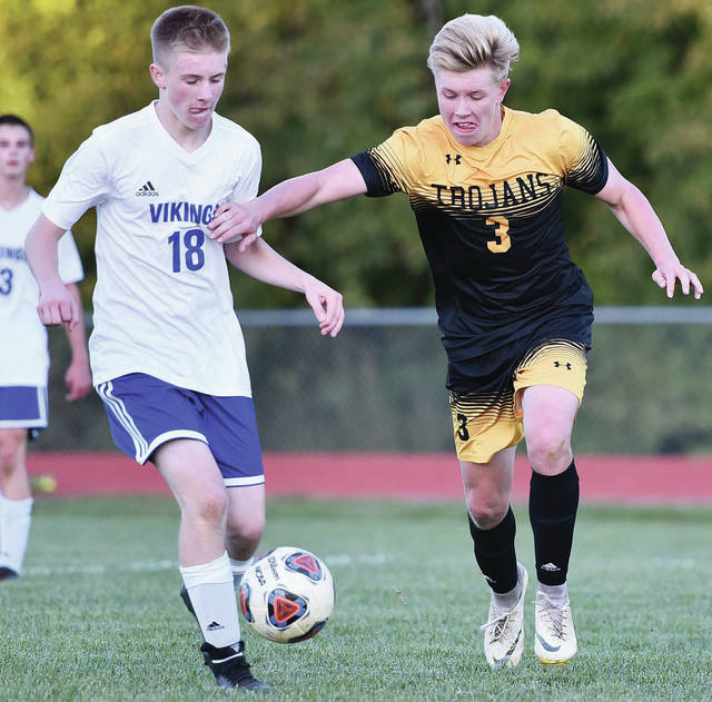 Botkins' Zane Paul works to get past Miami East's Jakob Demmit during a Division III sectional opener on Oct. 18, 2018 in Botkins. Paul, who scored 23 goals last year, is one of 10 returning starters for the Trojans. Botkins has won 10 consecutive Western Ohio Soccer League titles.