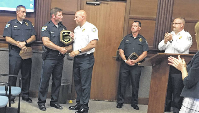 Sidney Police Capt. Jerry Tangeman, from left, looks on as Officer Andrew Shappie shakes Assistant Fire Chief Eric Barhorst's hand, next to Sgt. Jeremy Lorenzo and Fire Chief Brad Jones, after the officers were presented the fire department's Life Saver Award during the Sidney City Council meeting Monday night. The three officers were honored for their actions on April 10, 2019, in saving an elderly man and his two dogs from his burning Old English Court home.