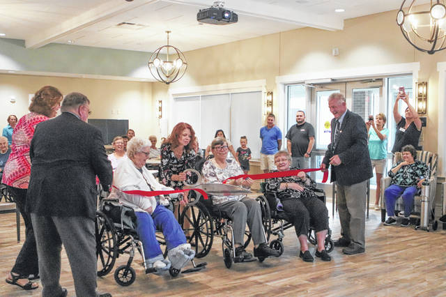 Shelby County Commissioner Julie Ehemann, center, cuts the ribbon opening the new addition at Fair Haven Monday night. Holding the ribbon are, left to right, Commissioner Bob Guillozet, Fair Haven Administrator Anita Miller, residents Phyllis Curl, Deborah Schaffner and Mary Rickert, and Commissioner Tony Bornhorst. The three residents are Resident Council officers.