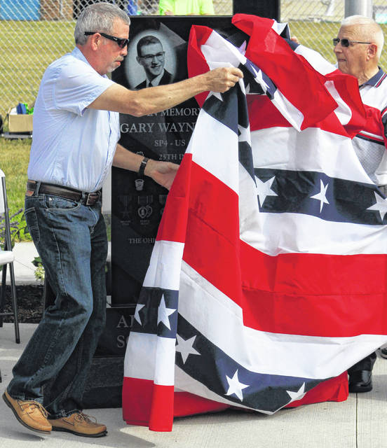 Family members Brent Christler, left, and Jim Knoch remove the flag that covering the new monument.