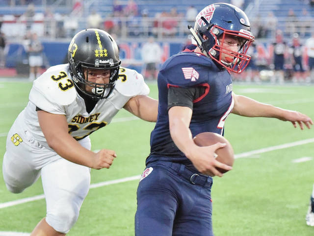 Sidney's Jaden Swiger lunges for Piqua quarterback Blane Ouhl during a Miami Valley League game on Friday at Alexander Stadium in Piqua.