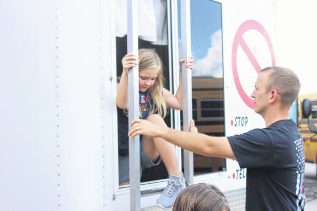 """Anna Fire Department Brigade Leader Bryan Doak assists Celia Brandewine, age 7, as she practices climbing out a window and down a ladder at an educational """"Smoke House"""" program at Anna Elementary School. Celia is the daughter of Amanda and Brian Brandewine, of Anna."""
