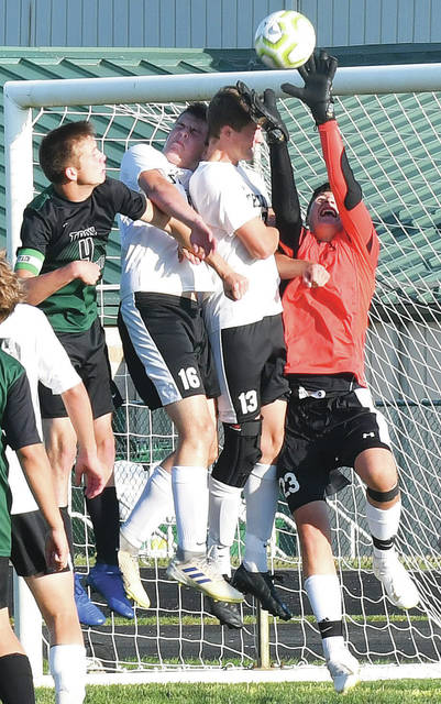 Botkins' goalkeeper Carson Motter, far right, deflects the ball during a nonconference game on Tuesday in Troy. Motter, a freshman, had six saves in the Trojans' 2-0 victory over state-ranked Troy Christian.