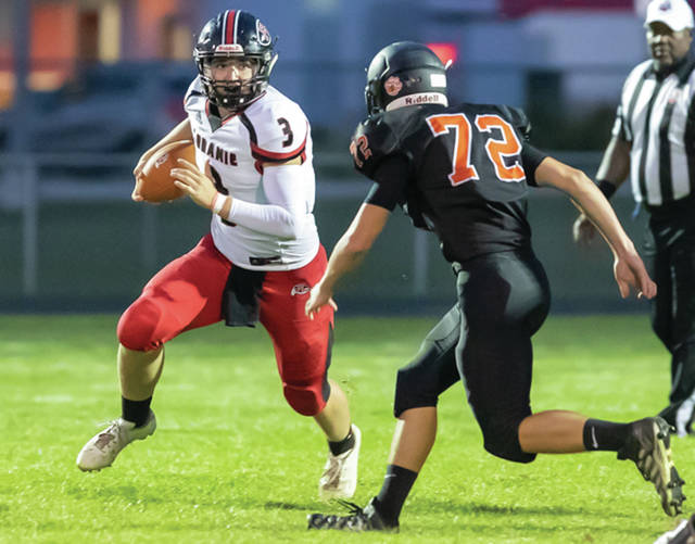 Fort Loramie quarterback Collin Moore runs and tries to avoid Minster's Craig Monnin during a nonconference game on Aug. 30 in Minster. Moore has thrown for a little over 500 yards and five touchdowns.