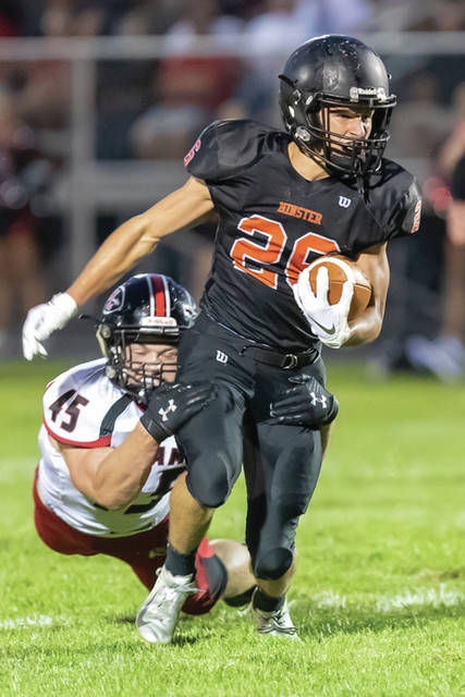 Minster's Brendan Bornhorst runs as Fort Loramie's Max Hoying tires to tackle him during a nonconference game on Friday at Minster Memorial Field.