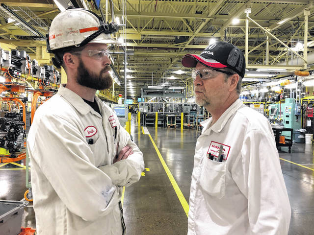 Honda Associate Mike Foulkes, right, talks with his son, Kevin, also a Honda associate, during the change of shifts when dad is leaving work and son is coming to work at the Anna Engine Plant.