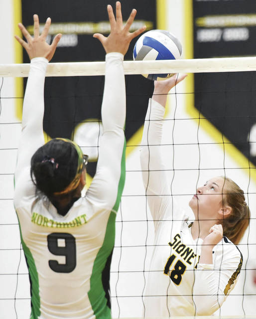 Sidney's Anna Brady spikes as Northmont's Alexis Boykin defends during a nonconference volleyball match on Saturday in Sidney.