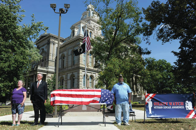 "Standing silent watch for veteran suicide awareness on the courtsquare are, left to right, Roxanne and Jack Curl and Gary, ""Tiny"" Stockton. Volunteers took turns standing next to a flag draped coffin to bring awareness to veterans' suicides and prevention. The watch held on Sunday, Sept. 22 was sponsored by they Shelby County Veteran Service Commission and supported by the American Legion and VFW posts of Shelby County and the DAV Chapter 48. The watch went from 6 a.m. to 6 p.m.."