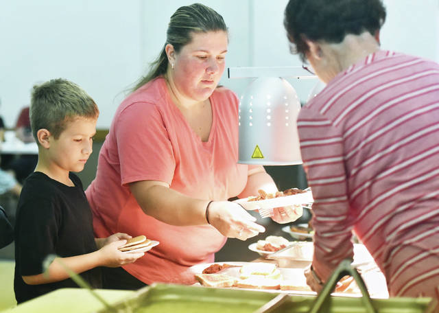 Maison Epley, left to right, 9, and his mom, Rosalynda Epley, get help dishing up breakfast from Elks Auxiliary member Linda Meininger, all of Sidney, during the Shelby County 4-H Foundation Annual Breakfast held at the Sidney Elks BPOE 786 on Sunday, Sept. 8. Served at the 4-H fundraiser were sausage links, bacon, eggs, pancakes, home fries, sausage gravy, biscuits, toast and a drink. Maison is a member of the 4-H club Starting Farmers and is the son of Timothy Epley.