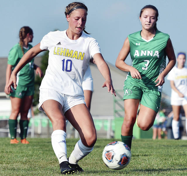 Lehman Catholic's Ella Monnin, left, passes as Anna's Taylor Kauffmann trails during a Western Ohio Soccer League game on Thursday in Anna. Kauffmann scored Anna's first goal in the 2-0 win.