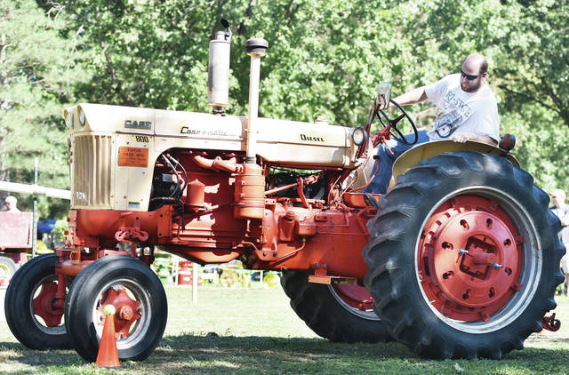 Derek Mescher, of Fort Loramie, tries to get his 1958 Case 800 tractor tire right next to an orange cone without knocking off the tennis ball on top during a competition at the Lake Loramie State Park Fall Harvest Festival on Saturday, Sept. 14.