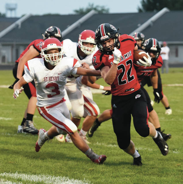 Fort Loramie's Damon Mescher runs past St. Henry's Jaden Lange during a nonconference game against St. Henry on Friday in Fort Loramie. Mescher scored two touchdowns in the game.