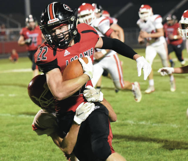 Fort Loramie's Damon Mescher struggles for extra yardage during a nonconference game against St. Henry on Friday in Fort Loramie. The Redskins had 418 yards of offense in their 42-7 win over St. Henry.