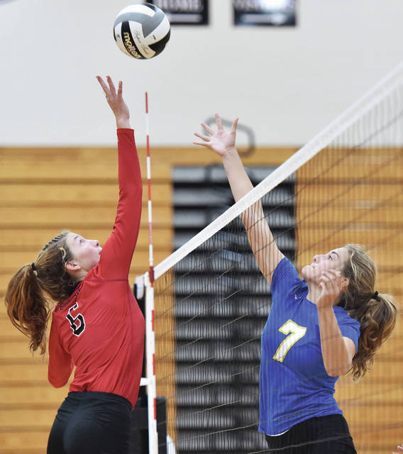 Fort Loramie's McKenzie Hoelscher, left, defends against Russia's Jessica York during a Shelby County Athletic League volleyball match on Thursday in Fort Loramie.