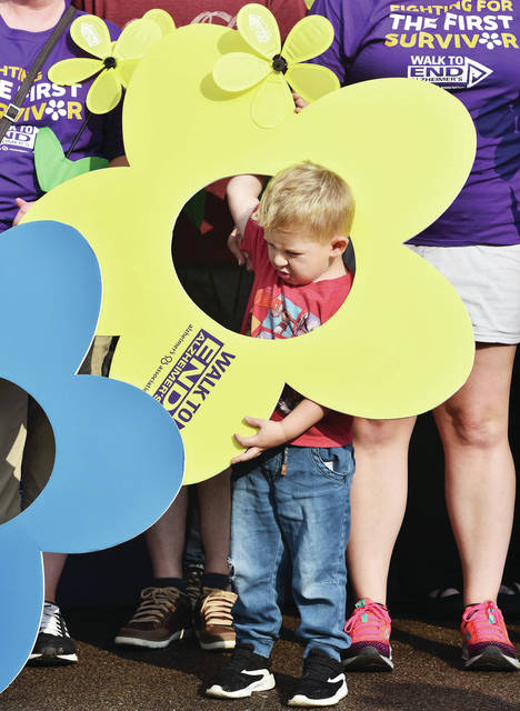 Elliott Jenkins, 3, of Sidney, son of Kya and Zachary Jenkins, struggles with a flower cutout during the 2019 Shelby County Walk to End Alzheimer's at Flanagan Sports Complex on Saturday, Sept. 21. Jenkins is a member of Anthony's Against Alzheimer's.