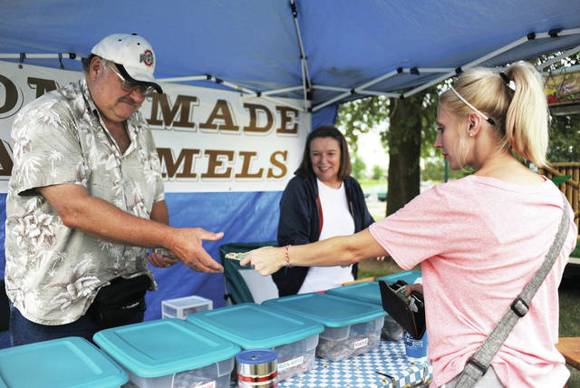 Mike, left to right, and Laura Hunsaker, sell their homemade caramels to Alicia Ziller, of Anna, at the Anna Park Festival on Saturday, Aug. 31.