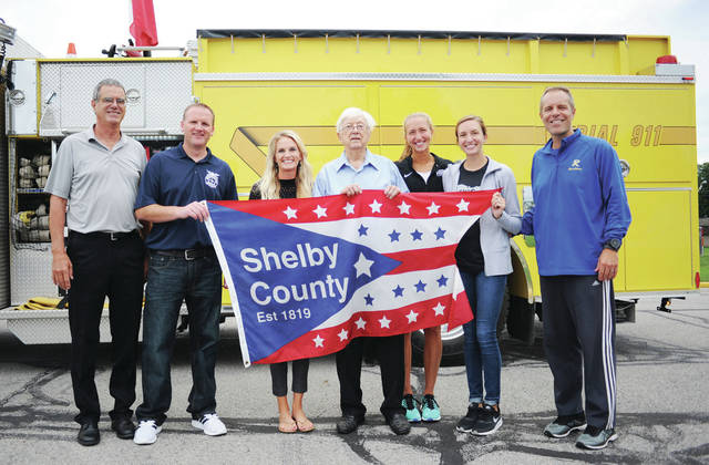 The people that took turns carrying the Shelby County flag to the Russia Homecoming Festival stand with the flag they carried on Saturday, Aug. 31.