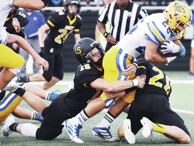 Sidney's Ryan Cagle, left, and Clay Carter bring down St. Marys' Ty Schlosser during a nonconference game on Friday at Sidney Memorial Stadium. Cagle, a senior, led Sidney with 9.5 tackles in the game while Carter had 3.5.