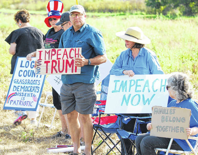 Democrats from five northwest Ohio counties gathered near Pratt Industries in Wapakoneta Sunday in the hope that President Donald Trump would see their protest signs as he passed by.